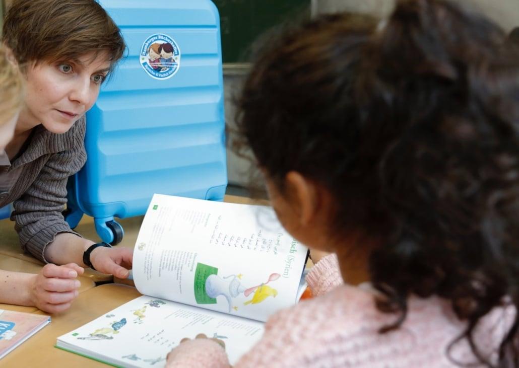 Sultany liest zusammen mit einem Kind